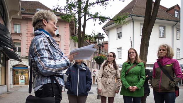 Stadtführerin Emma Anna Studer erzählt und vier Frauen hören zu.