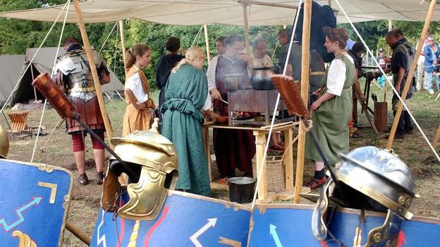Imbissstand mit Menschen in Kleidung aus der Römerzeit davor.