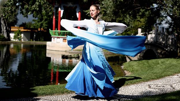 Sonja Rösli tanzt in traditioneller Tracht in einem chinesischen Garten.