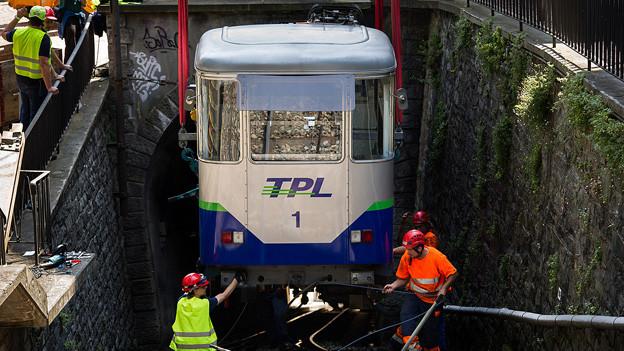 Arbeiter hieven die Standseilbahn mithilfe eines Krans aus den Schienen.