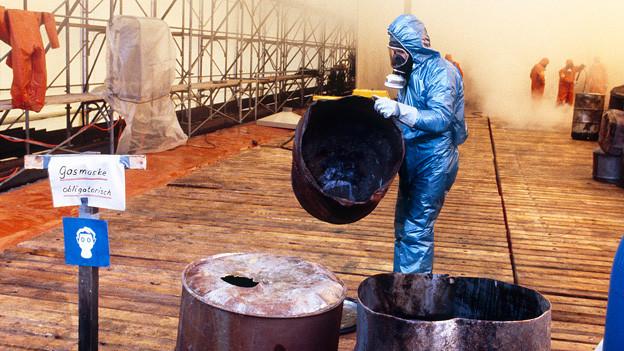 Mann in Schutzanzug und Schutzmaske mit ausgebrannten Fässern.