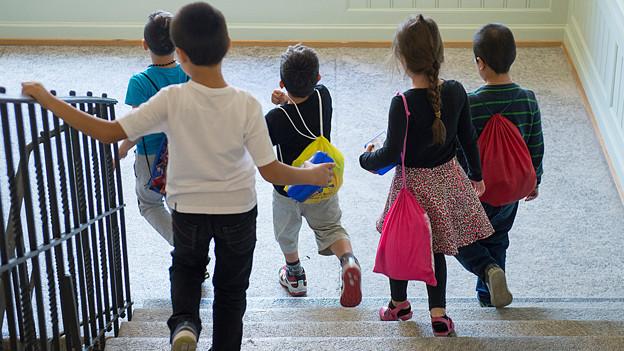 Schulkinder rennen die SChulhaustreppe hinunter.