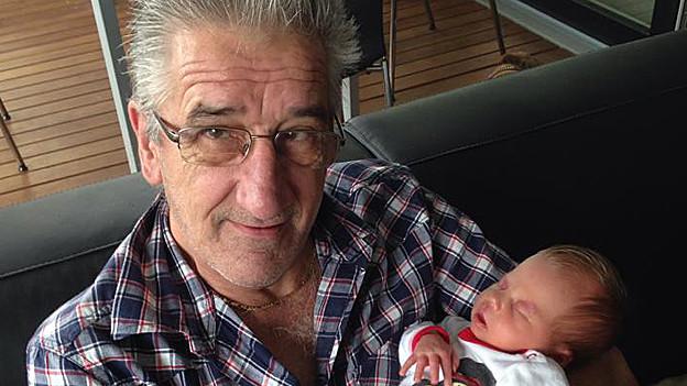 Hans Peter Rhyner mit Baby im Arm.