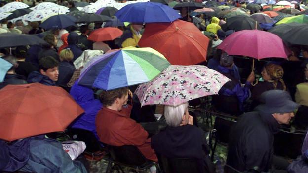 Openair-Besucher mit Regenschirm.