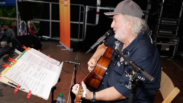 Peach Weber auf der Bühne mit Gitarre und Notenständer.