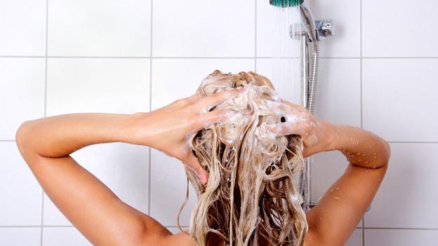 Frau schamponiert die Haare unter der Dusche.