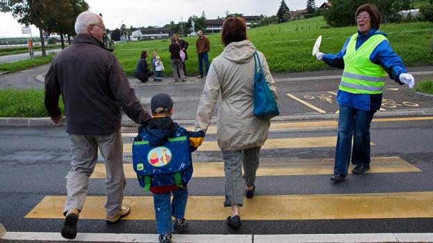 Verkehrslotse hilft Kind über die Strasse.