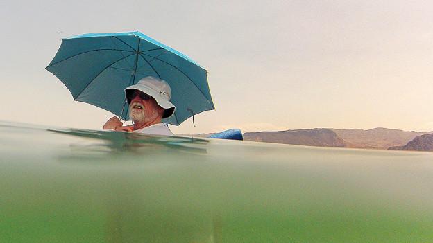 Mann schwimmt mit Schirm im Wasser.