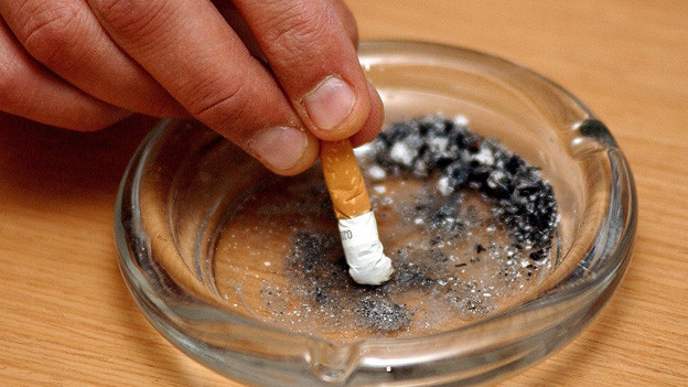 Jemand drückt eine Zigarette im Aschenbecher aus.
