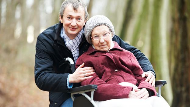 Ein Mann mit einer alten Frau im Rollstuhl.