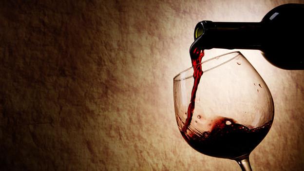 Aus einer Flasche wird Rotwein in ein Glas eingeschenkt.