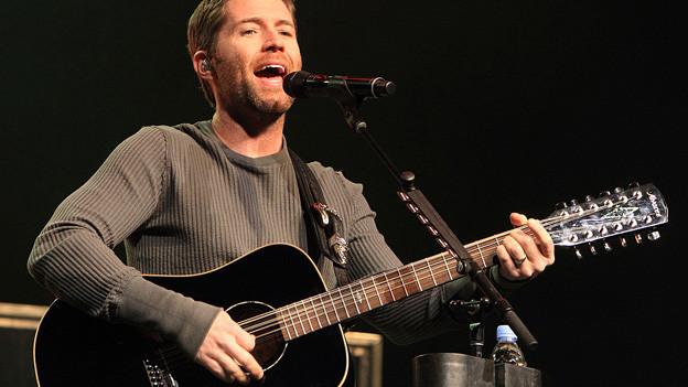 Josh Turner mit Gitarre auf der Bühne.