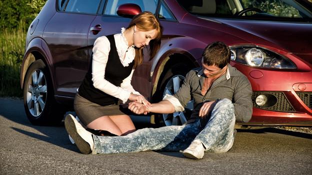 Eine Frau fühlt den Puls eines Mannes, der vor einem Auto sitzt.