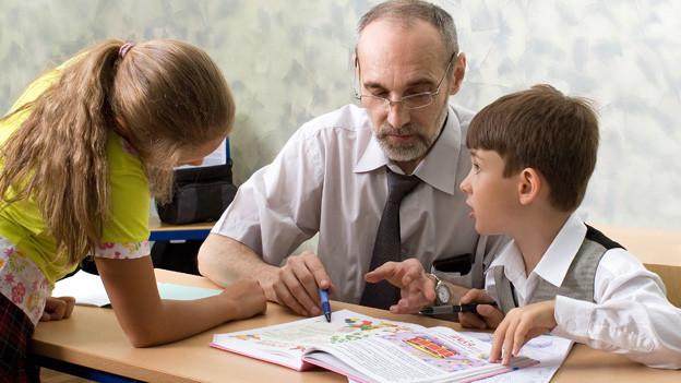 Älterer Herr im Klassenzimmer mit einem Schüler und einer Schülerin.