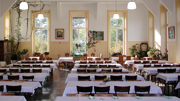 Grosser Esssaal mit Tischen mit weissen Tischtüchern.