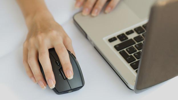 Frau am Laptop, eine Hand auf der Maus.