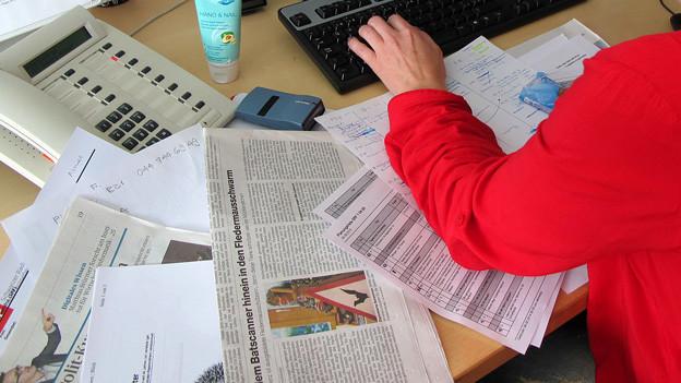 Chaotischer Arbeitstisch mit Zeitungen etc.