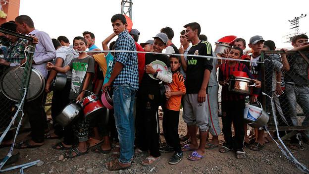 Flüchtlingskinder stehen Schlange.