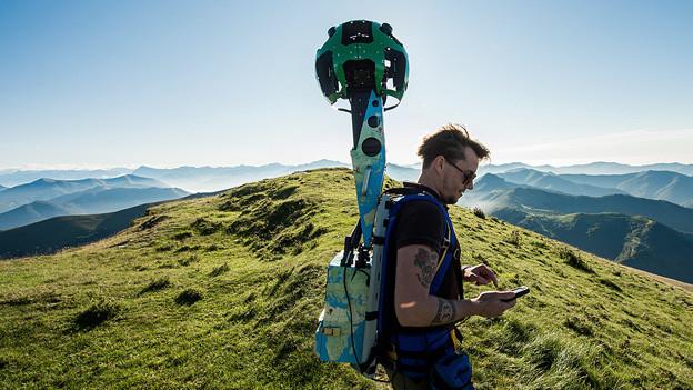 Ein Mann auf dem Monte Generoso trägt einen «Google Trekker» auf den Schultern.