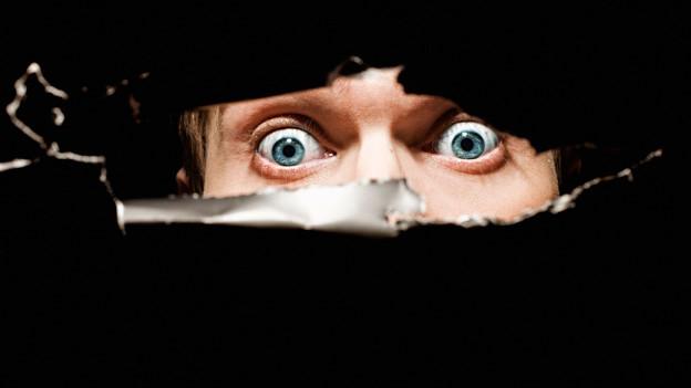 Zwei angsterfüllte Augen, rundum schwarz.