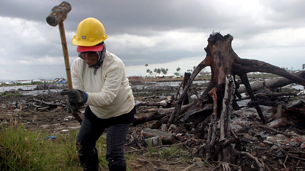 Frau in Indonesien arbeitet mit Hammer und Helm.