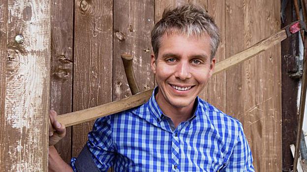 Porträtbild von Reto Scherrer vor einer Holzwand.