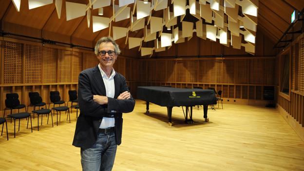 Bernhard Ley posiert vor einem Flügel in einem Musiksaal.