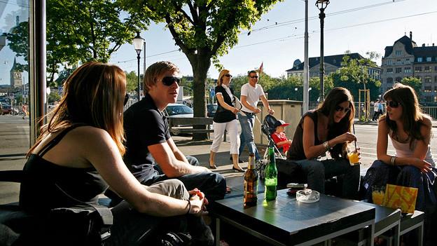 Vier Menschen geniessen das schöne Wetter in einer Lounge an der Limmat.
