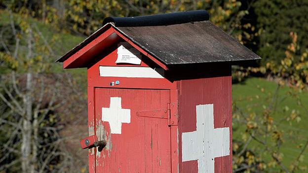 Holzbriefkasten im Schweizerflaggen-Design.