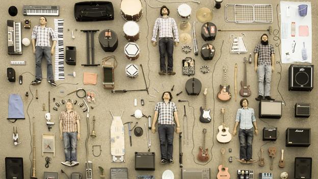 Die sechs Bandmitglieder liegen inmitten ihrer ausgebreiteten Instrumente und Zubehör.