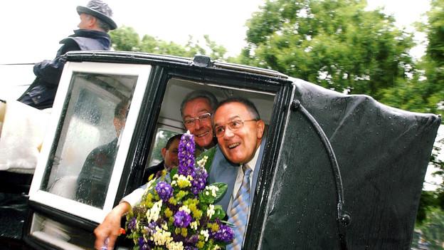 Röbi Rapp und Ernst Ostertag winken aus einer Kutsche.