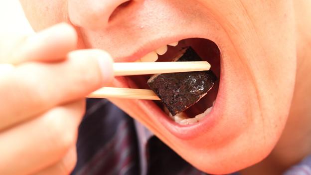 Ein man schiebt sich mit Essstäbchen ein Sushi in den Mund.
