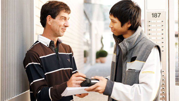 Junger Postbote reicht einem Kunden an der Haustüre den elektronischen Scanner zur Unterschrift entgegen.