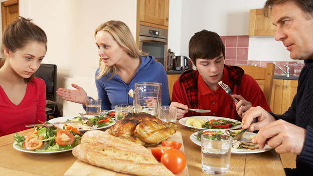 Eine vierköpfige Familie am Esstisch.
