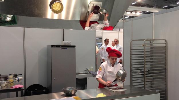 Eine Köchin ist in der Küche am Werk.