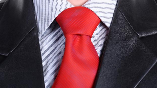 Rote Krawatte und schwarzer Lederkittel in der Nahaufnahme.