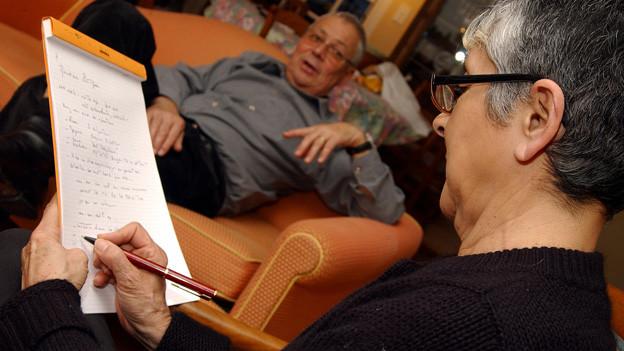 Ein Mann sitzt auf einem orangen Sofa in der Praxis einer Psychologin. Diese sitzt mit dem Notizheft auf einem Stuhl und schreibt.