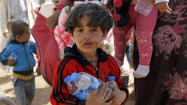 Syrisches Flüchtlingskind mit Wasserflasche in der Hand und traurigem Blick.