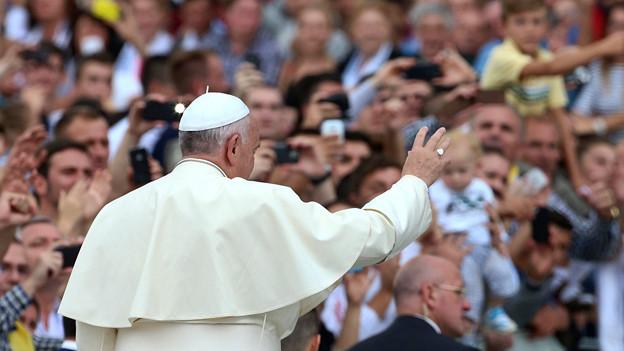 Papst Franziskus vor Menschen.