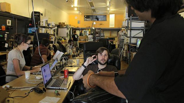 Computerspezialisten am Werk: Zwei diskutieren, weitere sitzen am Computer.