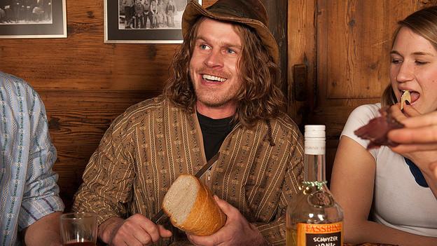 Franz Arnold sitzt mit Hut am Tisch und schneidet Brot.