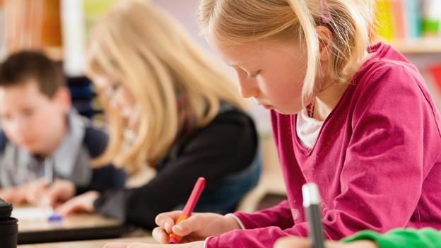 Schulkinder arbeiten am Pult, im Vordergrund ein blondes Mädchen.