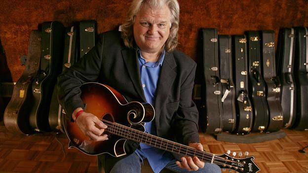 Ricky Skaggs posiert vor vielen Gitarrenkästen an der Wand.