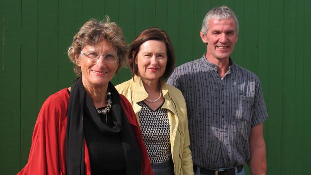 Katharina Kilchenmann mit ihren Gästen vor einer grüner Wand stehend.