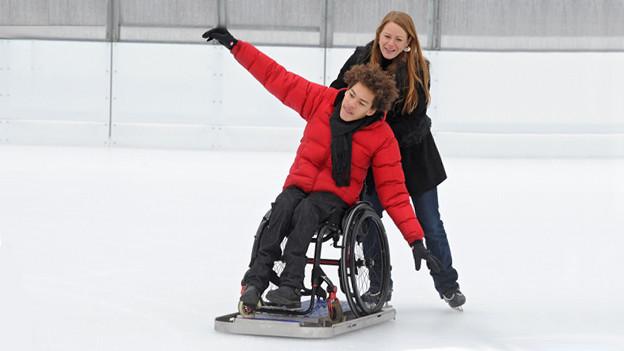 Unter dem Rollstuhl ist ein Eisgleiter montiert. Dies ermöglicht auch Rollstuhlfahrern das Schlittschuhfahren.