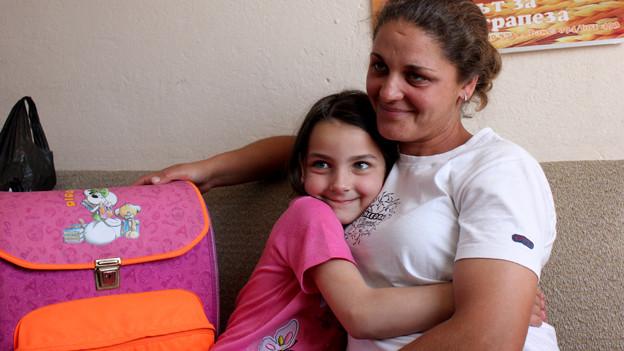 Mädchen und Mutter auf Sofa.