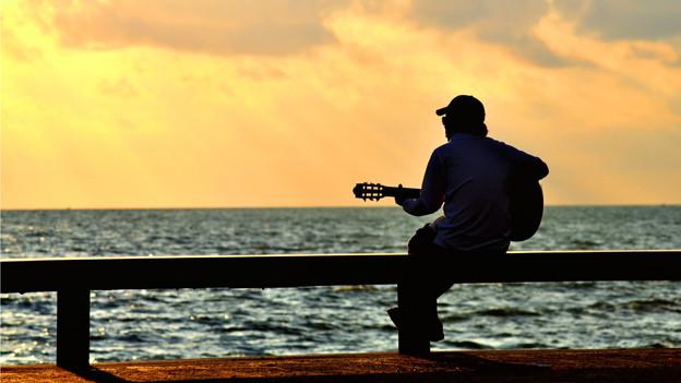 Mann sitzt mit Gitarre am Meer.