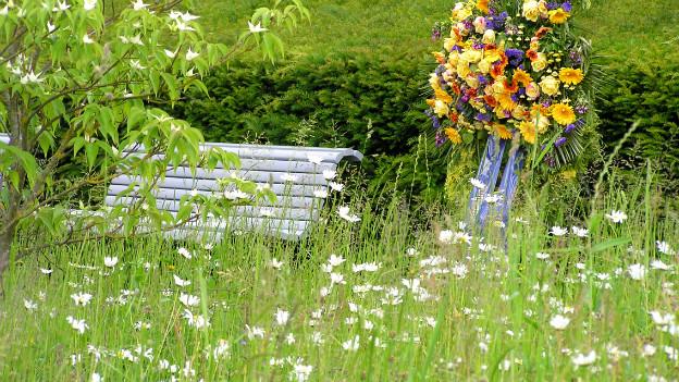 Im Vordergrund eine Blumenwiese, im Hintergrund ein Blumenkranz fürs Grab