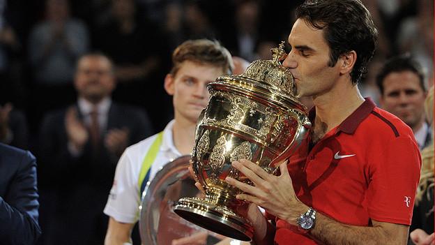 Roger Federer küsst den Pokal.