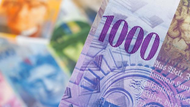 Eine Tausendernote im Vordergrund, mehr Schweizer Geldnoten unscharf im Hintergrund.